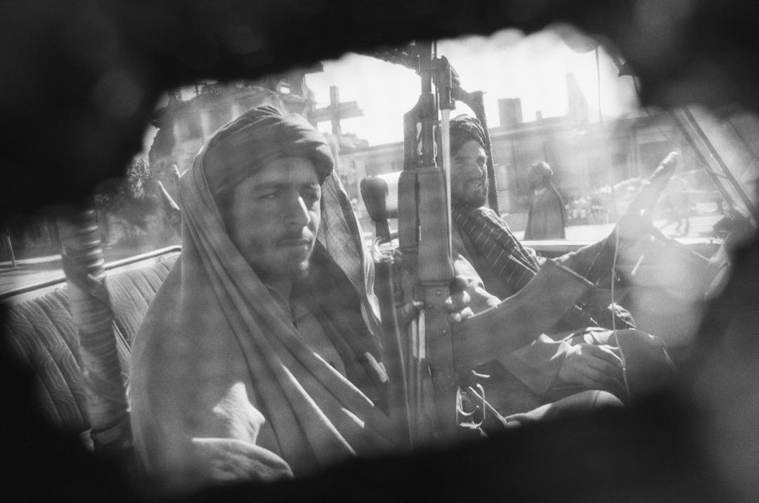 攝影師從罩袍下拍攝數名持槍的塔利班戰士。