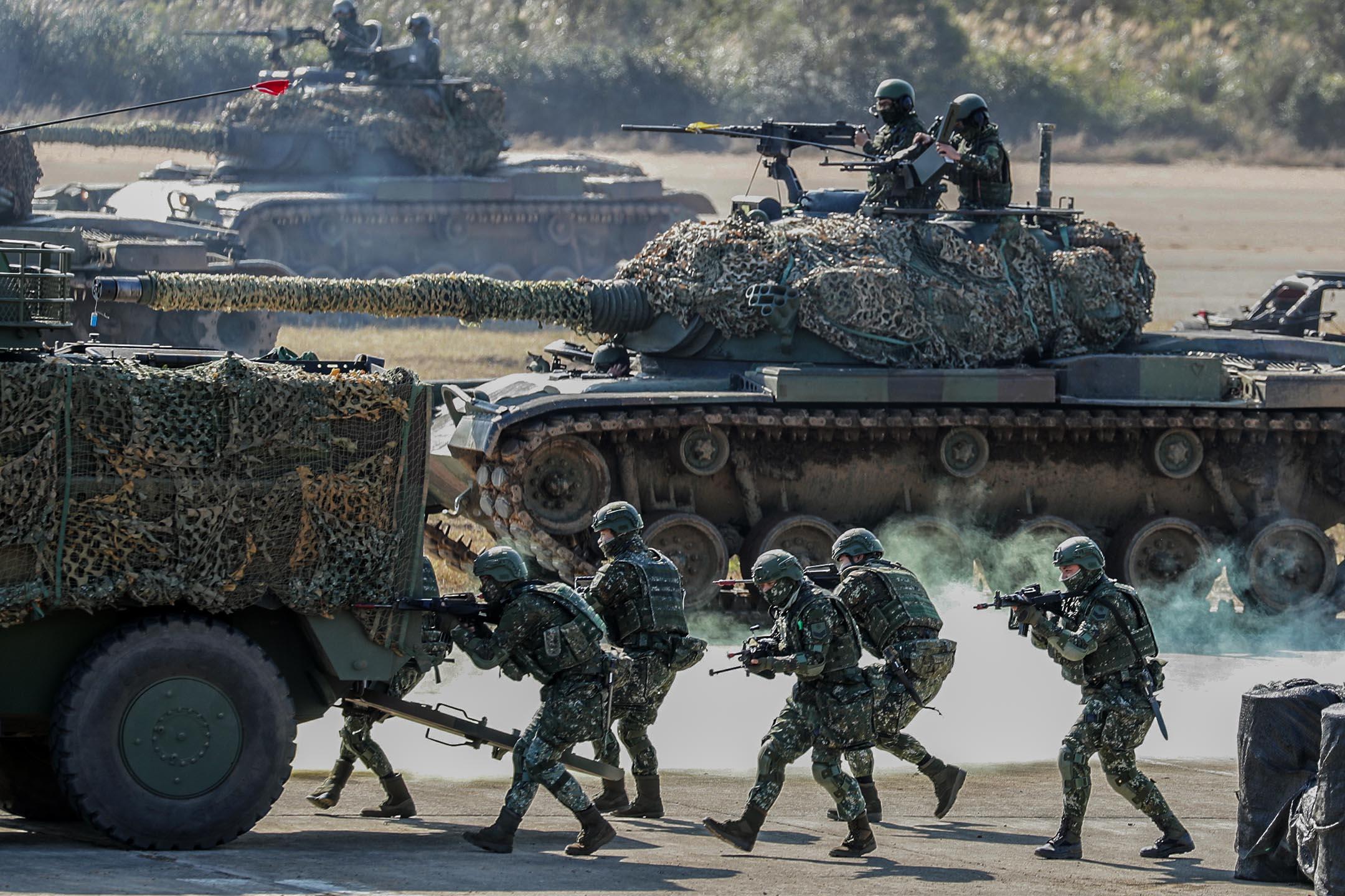 2021年1月19日台灣新竹縣舉行的一次軍事演習中,台灣武裝部隊成員走在軍車後面。 攝:I-Hwa Cheng/Bloomberg via Getty Images