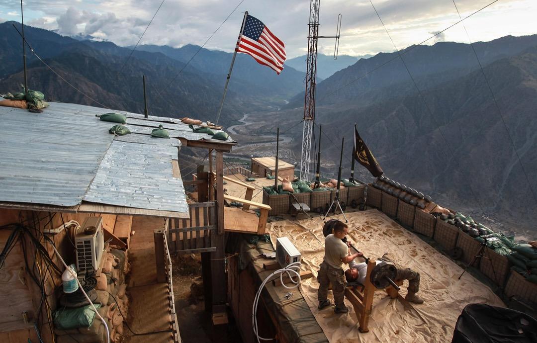 2011年9月2日,阿富汗東北部的庫納爾省,駐守山上一個哨站的美軍部隊隊員在舉重健身。該地區鄰近巴基斯坦,是當地塔利班武裝分子進入阿富汗的主要路線,亦因此經歷了戰爭中最激烈的戰鬥。