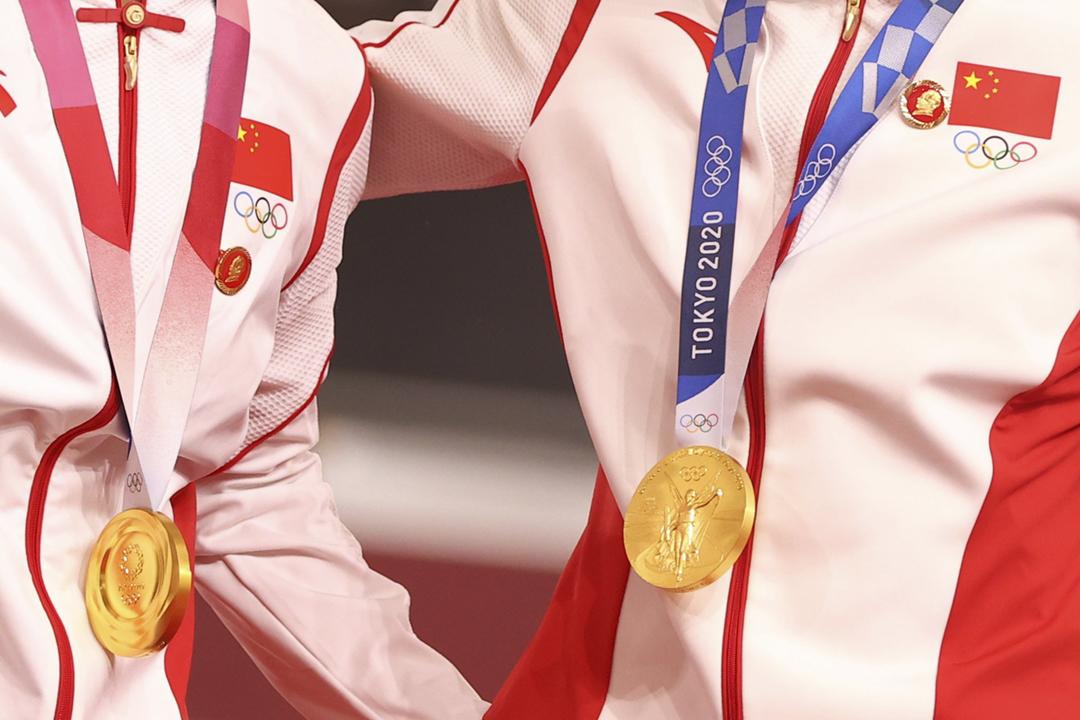 2021年8月2日,中國奧運代表團單車運動員鮑珊菊及鍾天使領取奧運獎牌時,衣襟上戴有毛澤東肖像襟章。 攝:Matthew Childs / Reuters