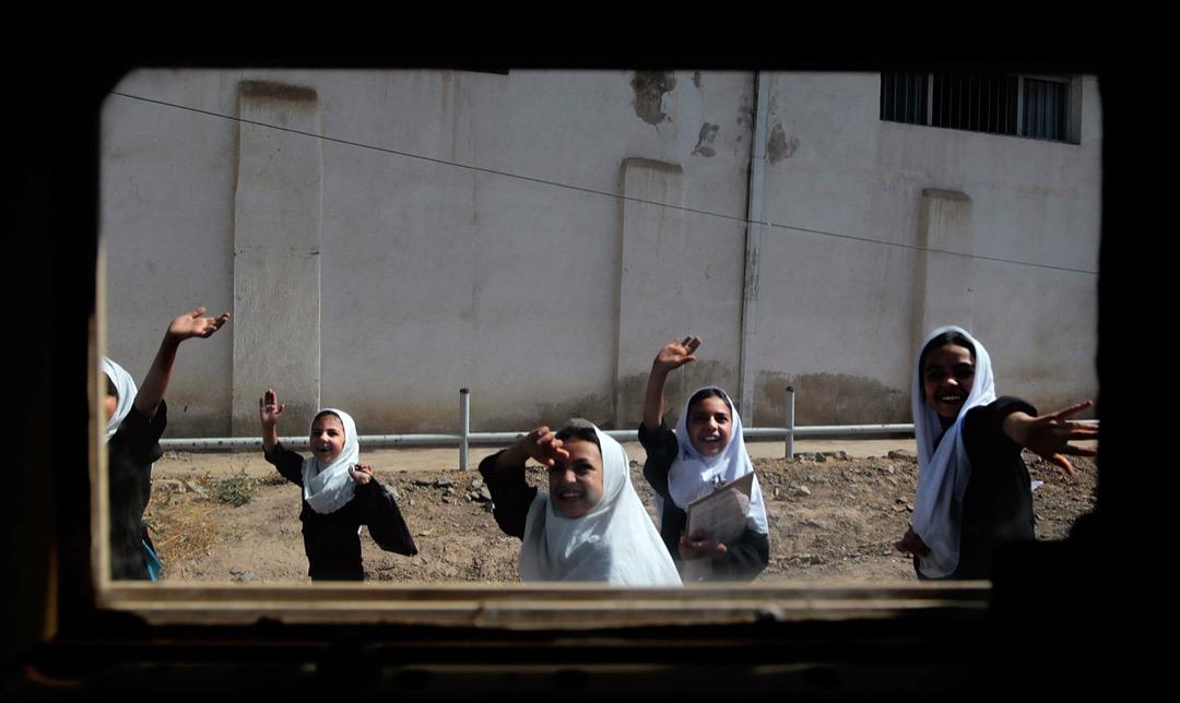 2010年6月26日,阿富汗第三大城市赫拉特,上學途中的女孩們向裝甲車內的美軍部隊揮手。