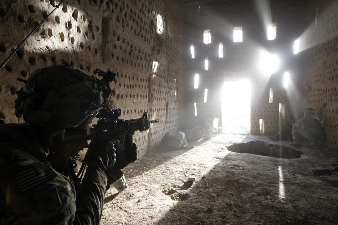 2012年4月26日,阿富汗南部坎大哈省,美軍第82空降師的步兵團士兵Nicholas Dickhut在Zharay區巡邏時遭到塔利班的射擊後,找建築物作掩護,將步槍對準門口。