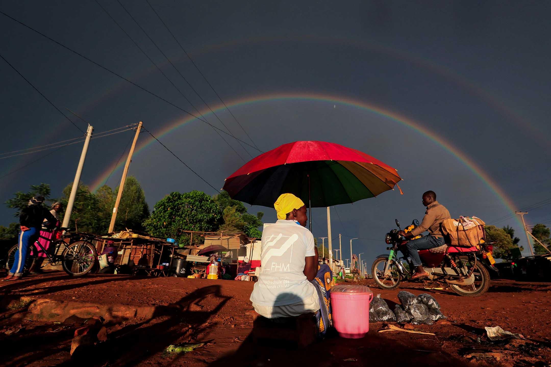 2020年5月3日肯尼亞,一名婦女手持雨傘並在路邊賣零食。