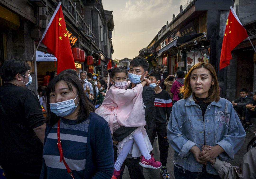 2020年10月3日,北京的黃金周假期,一名中國男子帶著身著傳統服裝的女兒在商業和旅遊區散步。