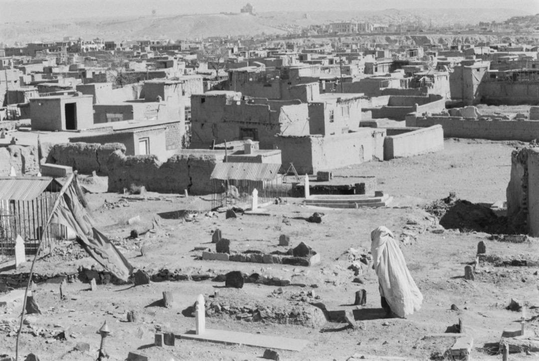 一名穿罩袍的女子在阿富汗一個墓地走過。