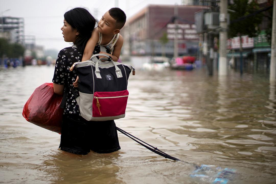 2021年7月23日,中國河南省鄭州市遭遇洪災,一名女士帶着孩子涉水而行。 攝:Aly Song / Reuters