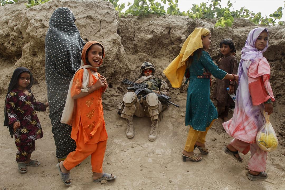 2011年6月13日,阿富汗坎大哈省本傑瓦伊區,數名女子行經一位在巡邏期間休息的加拿大士兵。