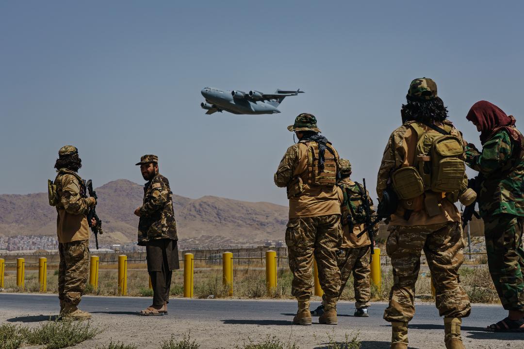 2021年8月30日,阿富汗首都喀布爾,美軍C-17飛機起飛,塔利班士兵在外圍警戒。 攝:Marcus Yam/Getty Images