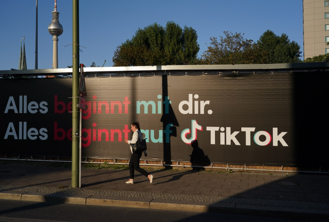 德國柏林,一名女子走過街頭一塊TikTok廣告牌。