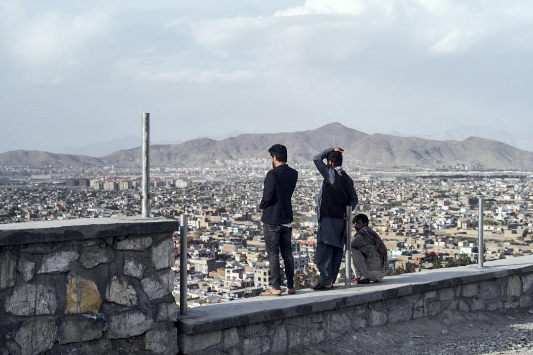 在喀布爾中南部的丘陵貧民窟地帶,幾名年輕人從高處眺望着城市腹地。
