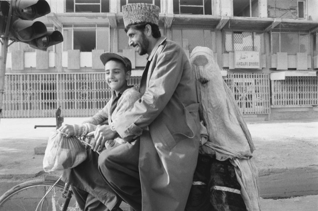 一名男子騎單車載著一名男孩和一位穿罩袍的女子穿梭阿富汗街頭。