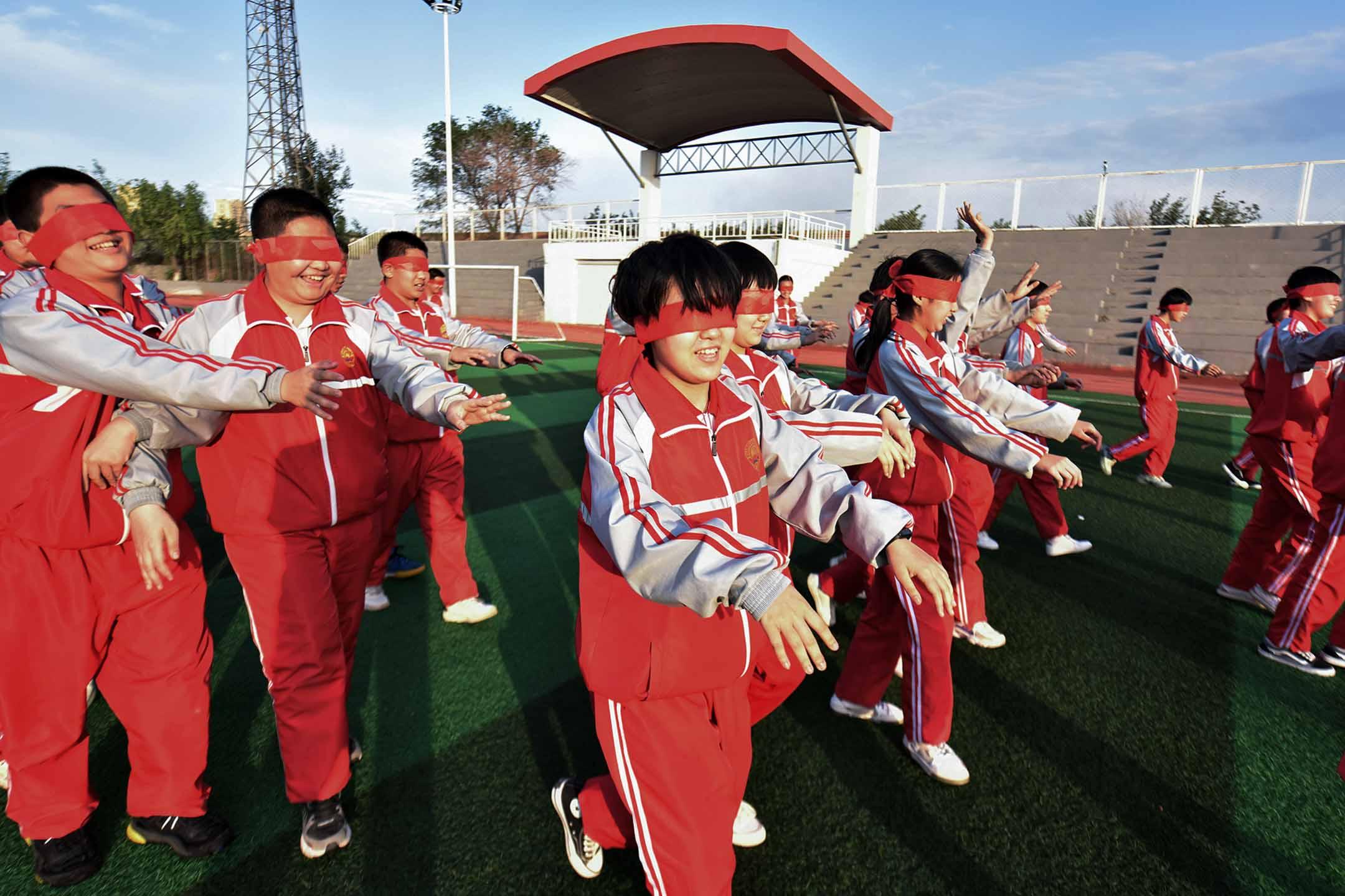 2021年6月2日中國張家口,學生們眼睛蒙著布向前走。