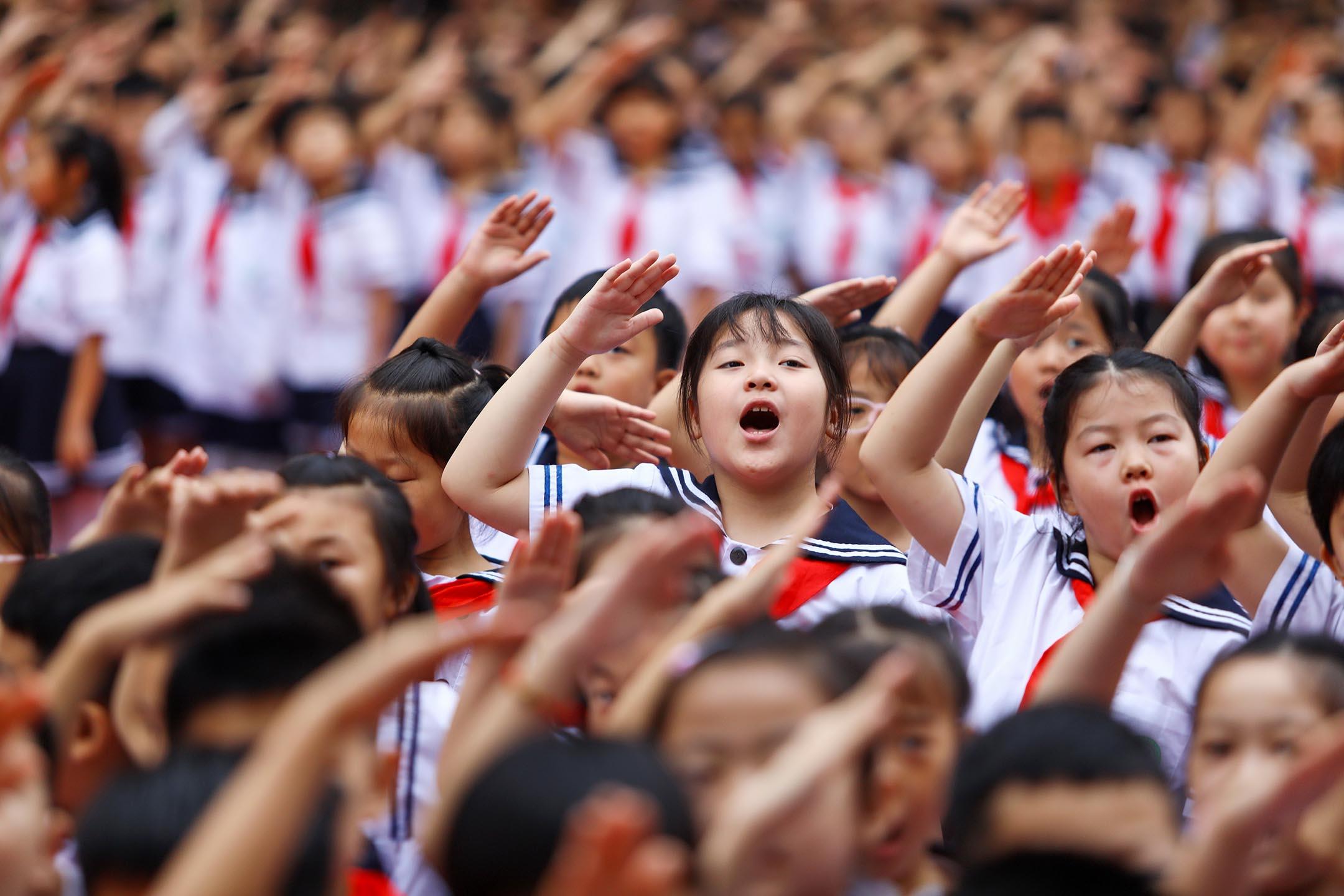 2021年9月1日中國淮北,新學期開學典禮上,小學生敬禮並唱國歌。