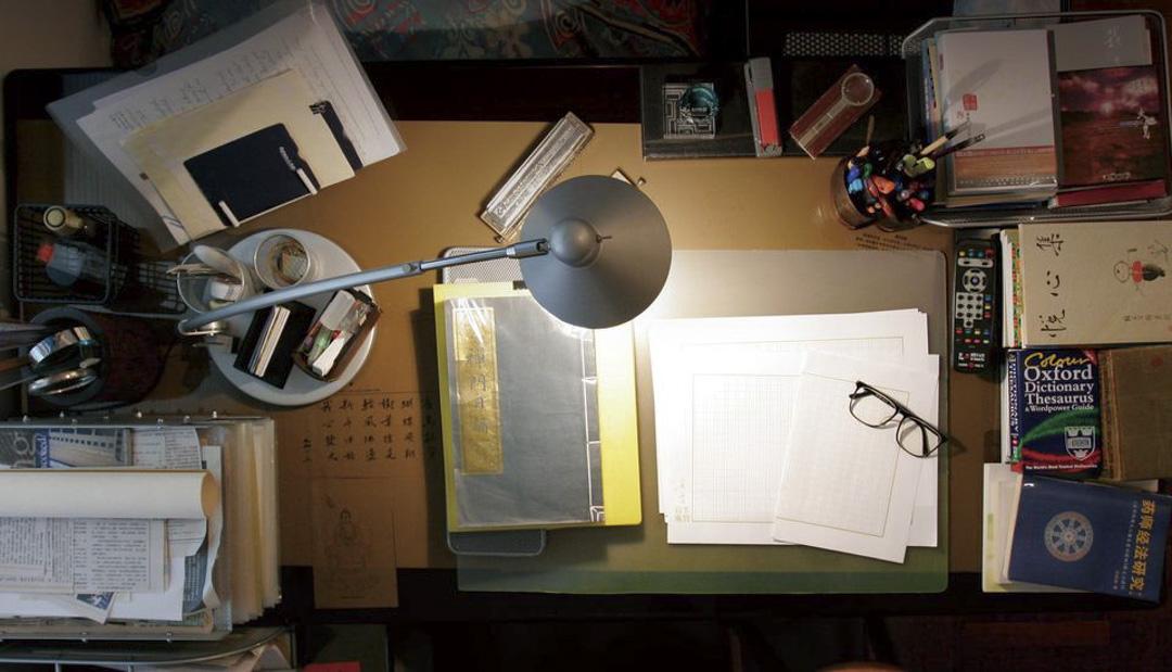 霑叔的書檯當眼之處,有眼鏡、放大鏡、口風琴和稿紙等。