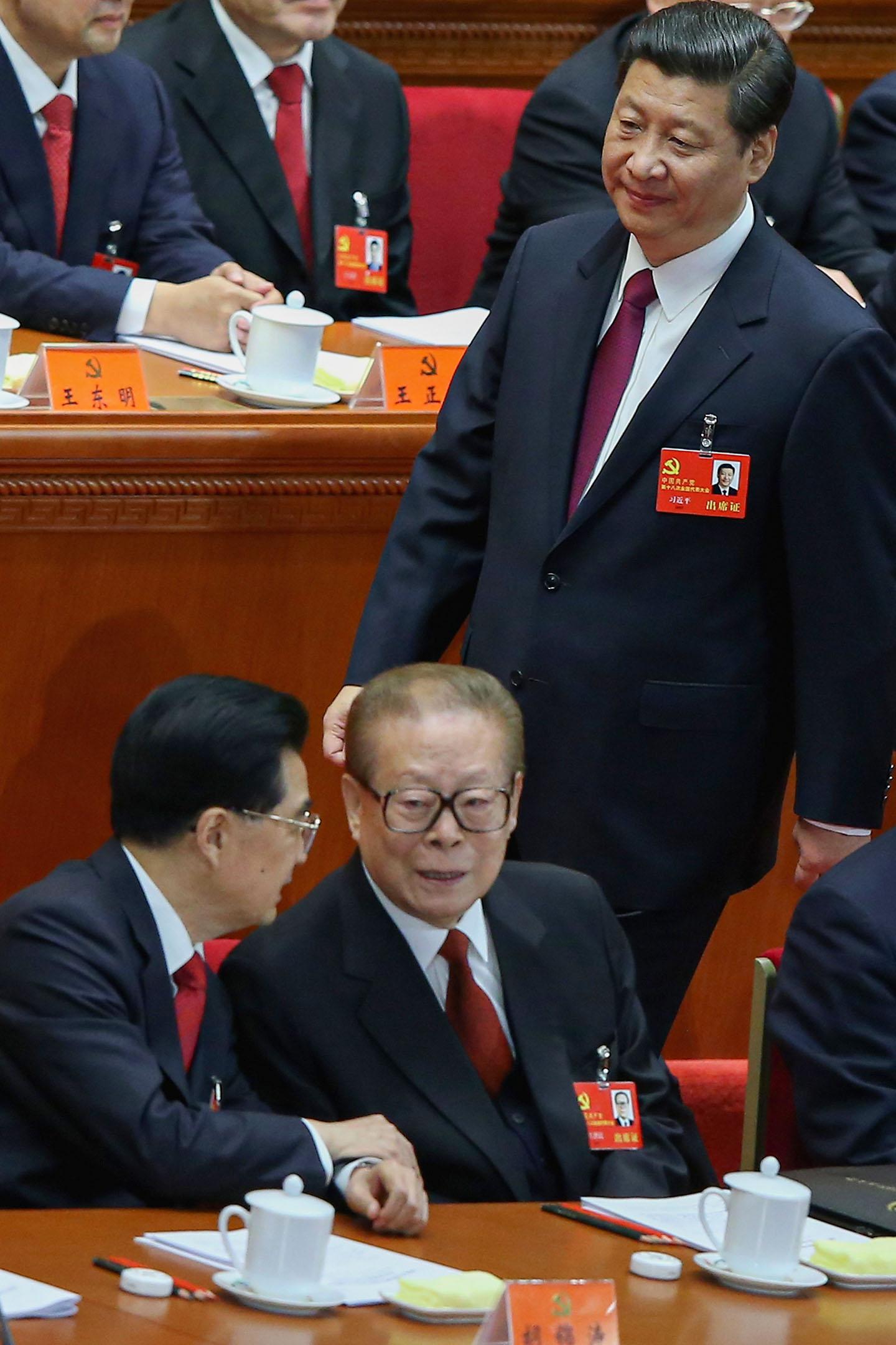 2012年11月8日中國北京,人民大會堂舉行的十八大開幕式上,中國國家副主席習近平走近中國國家主席胡錦濤(左)和中國前國家主席江澤民(右)。