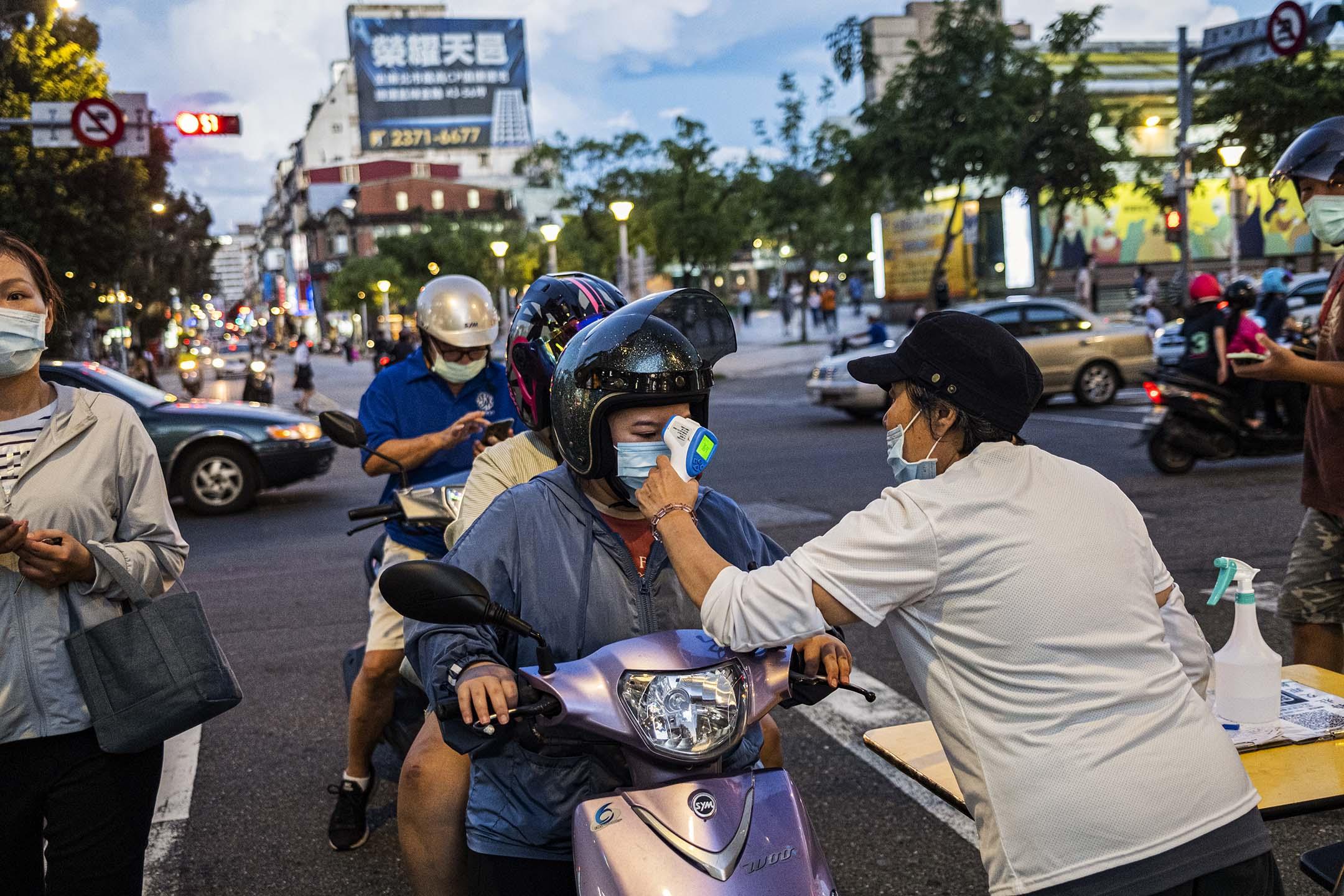 2021年9月10日台北龍山寺,市民進入夜市前要先檢查體温。 攝:陳焯煇/端傳媒