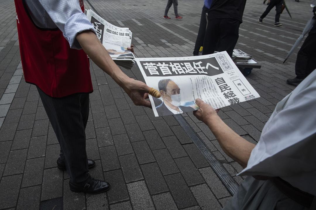 2021年9月3日在日本東京,一名民眾接過一份刊載菅義偉棄選自民黨總裁消息的號外。 攝:Hiro Komae / AP
