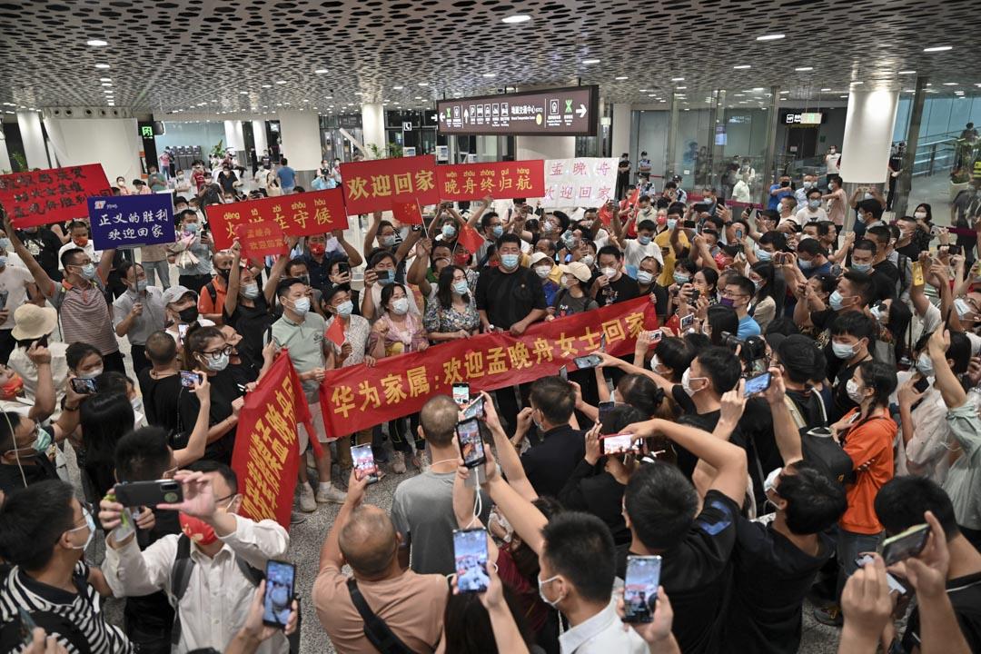 2021年9月25日,深圳人們在深圳寶安國際機場等待孟晚舟回國,舉著寫有「歡迎回家孟晚舟」的橫幅和標語牌。