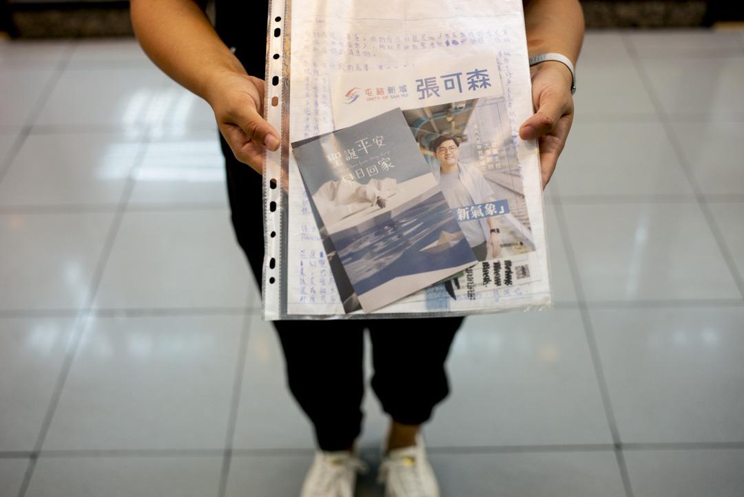 前議助阿欣手持張可森寄給她的信件及區議員單張。 攝:林振東/端傳媒