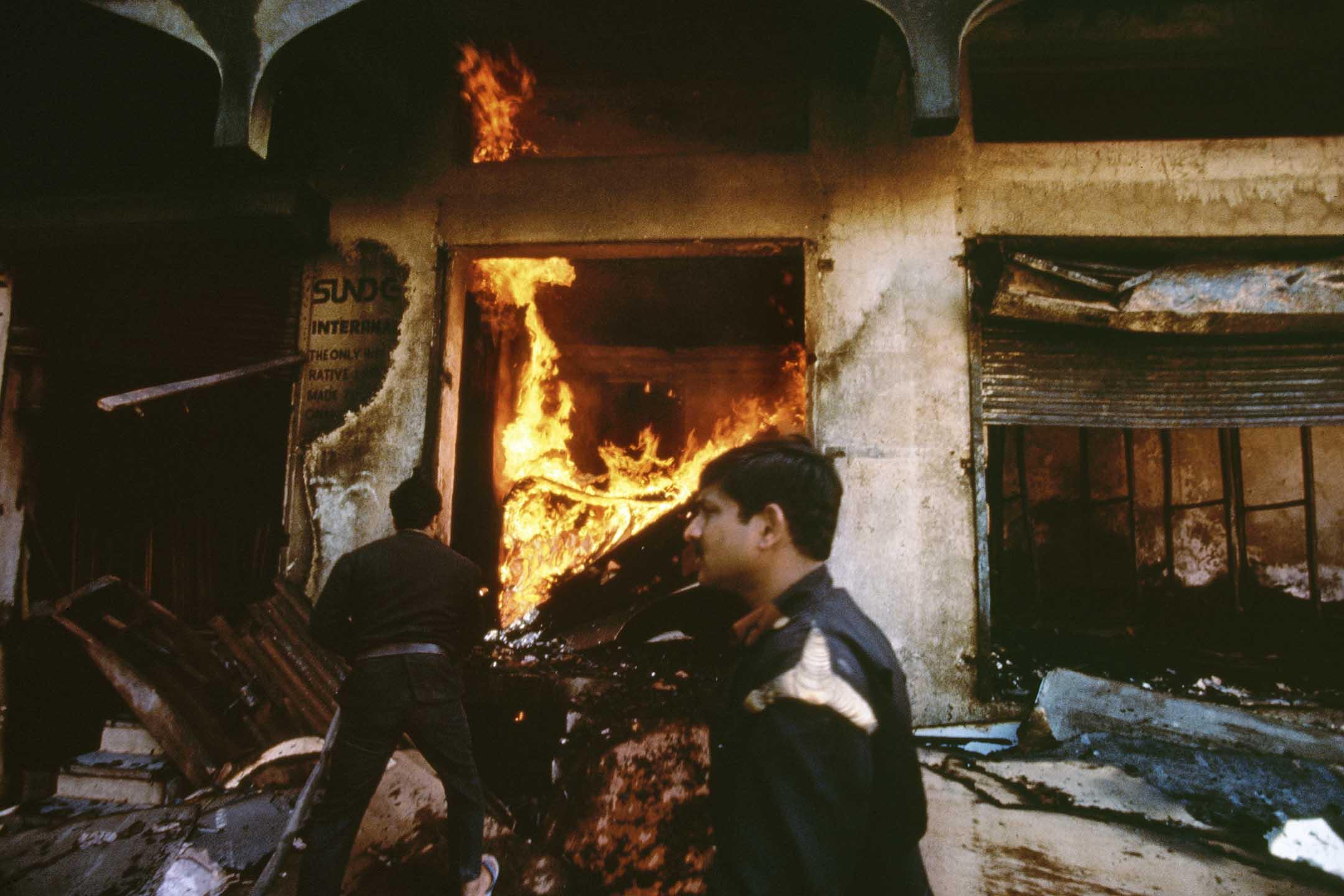 1993年1月13日印度孟買,消防員試圖救熄被印度教徒縱火點燃的商店。 攝:Robert Nickelsberg/Getty Images