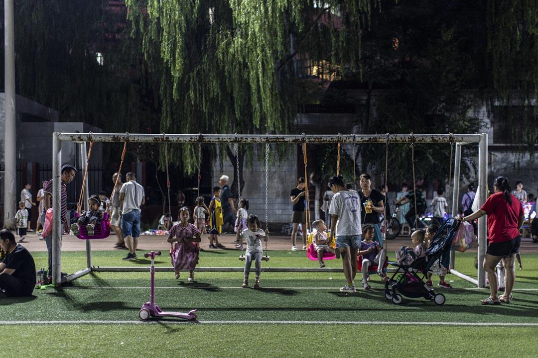 夜裏在操場玩耍的放暑假的孩子們。