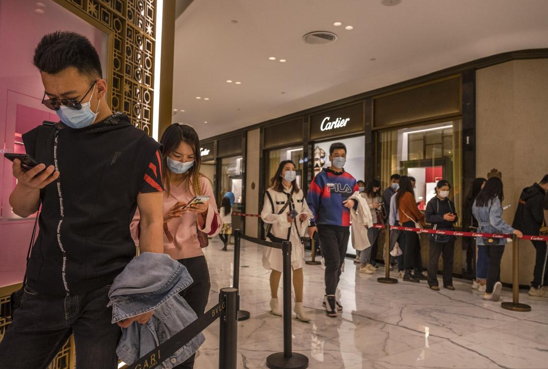 2021年4月18日,北京的年輕消費者在奢侈品店外等待進場時觀看手機。