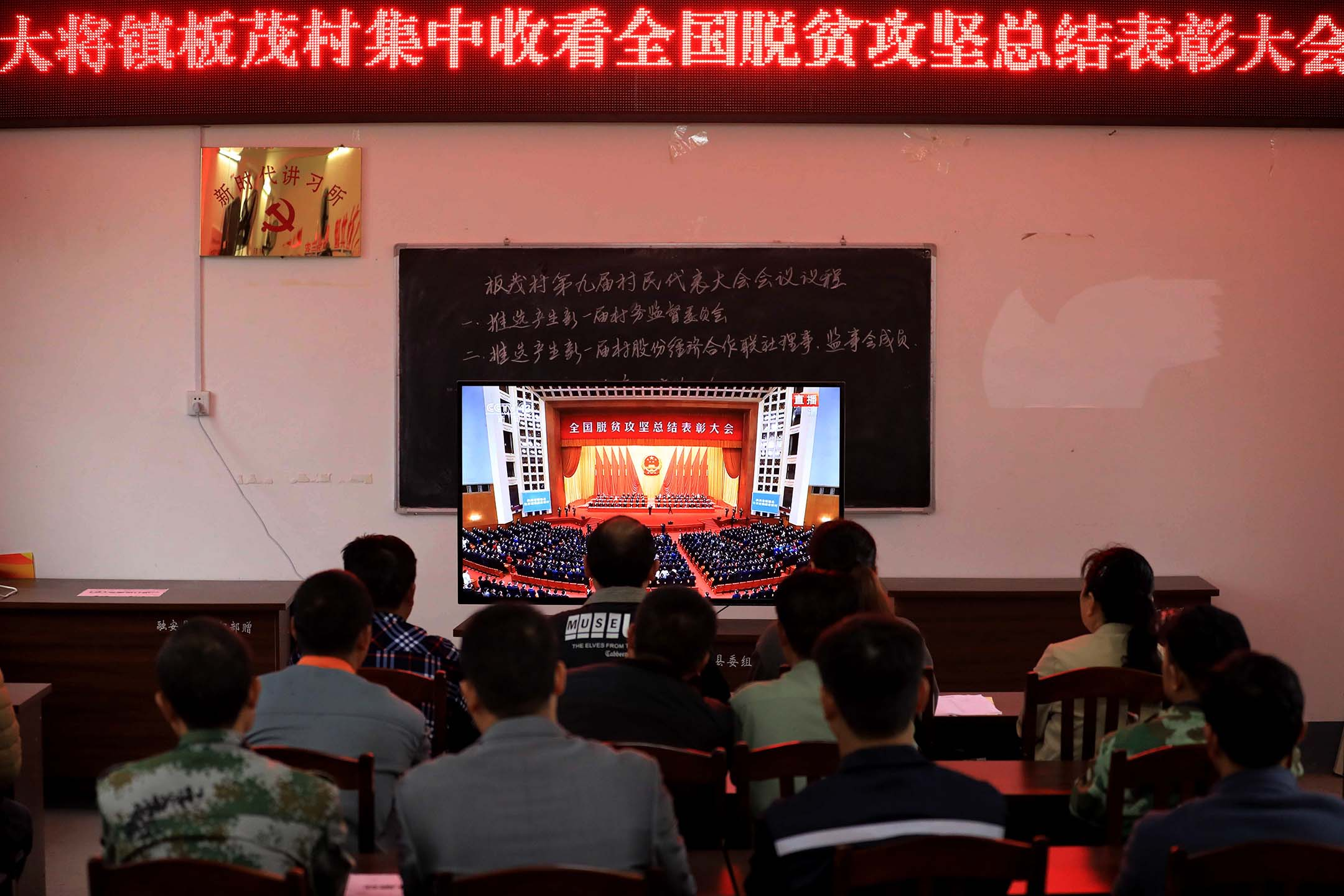 2021年2月25日中國柳州,中國共產黨成員觀看電視屏幕播放人民大會堂舉行的「全國脱貧攻堅總結表彰大會」。