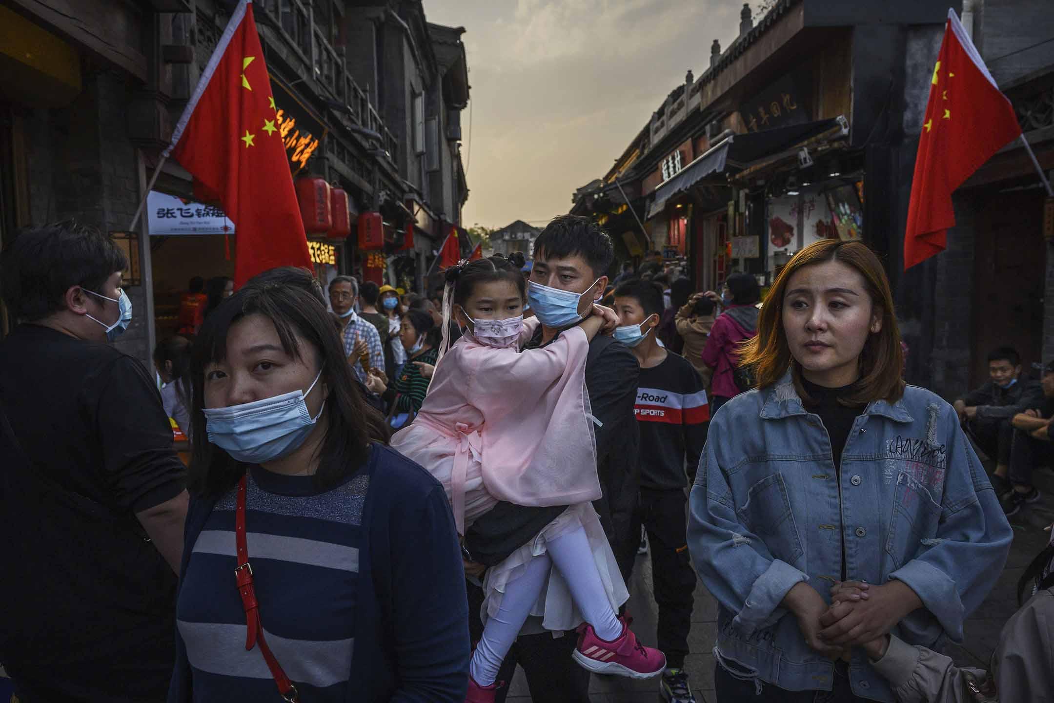 2020年10月3日中國北京,黃金周假期期間,一名中國男子帶著身著傳統服裝的女兒在旅遊區散步。