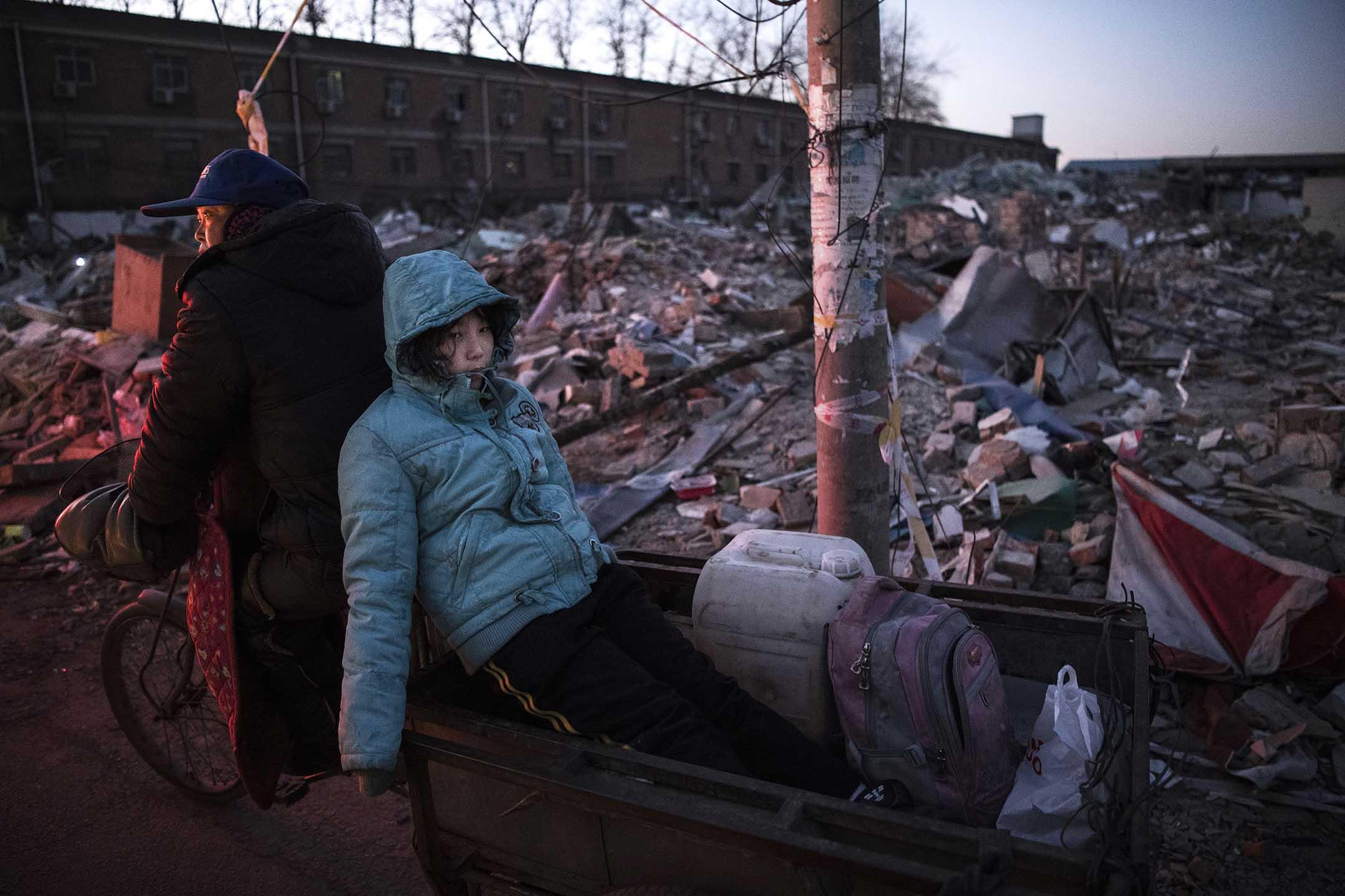 2017年12月4日中國北京,一名中國女孩坐在一輛踏板車的後面,經過政府拆除的建築物瓦礫,該地區曾經有住房和服裝市場。 攝:Kevin Frayer/Getty Images