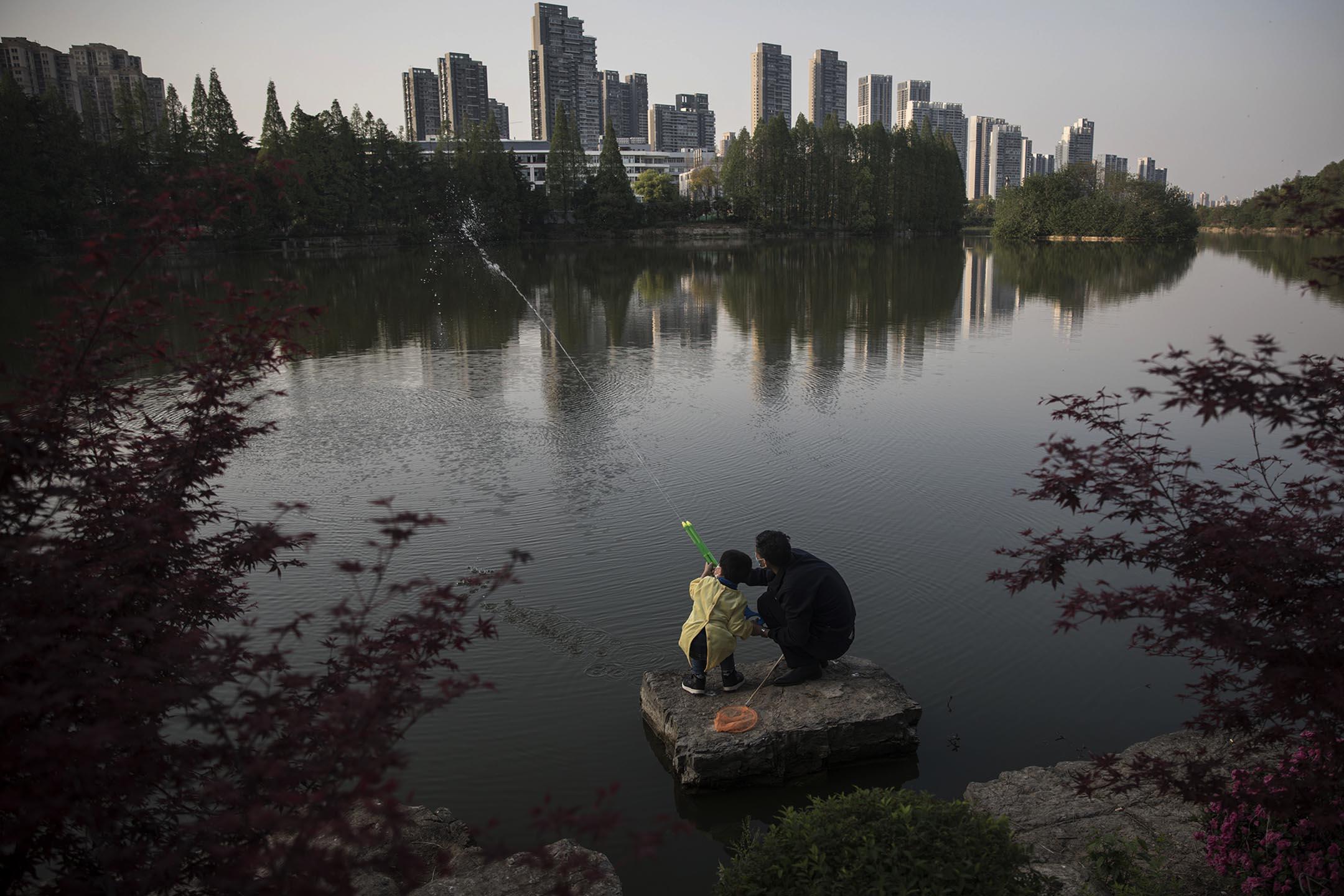 2020年4月9日中國武漢,一個男孩和他的爺爺在公園玩水槍。