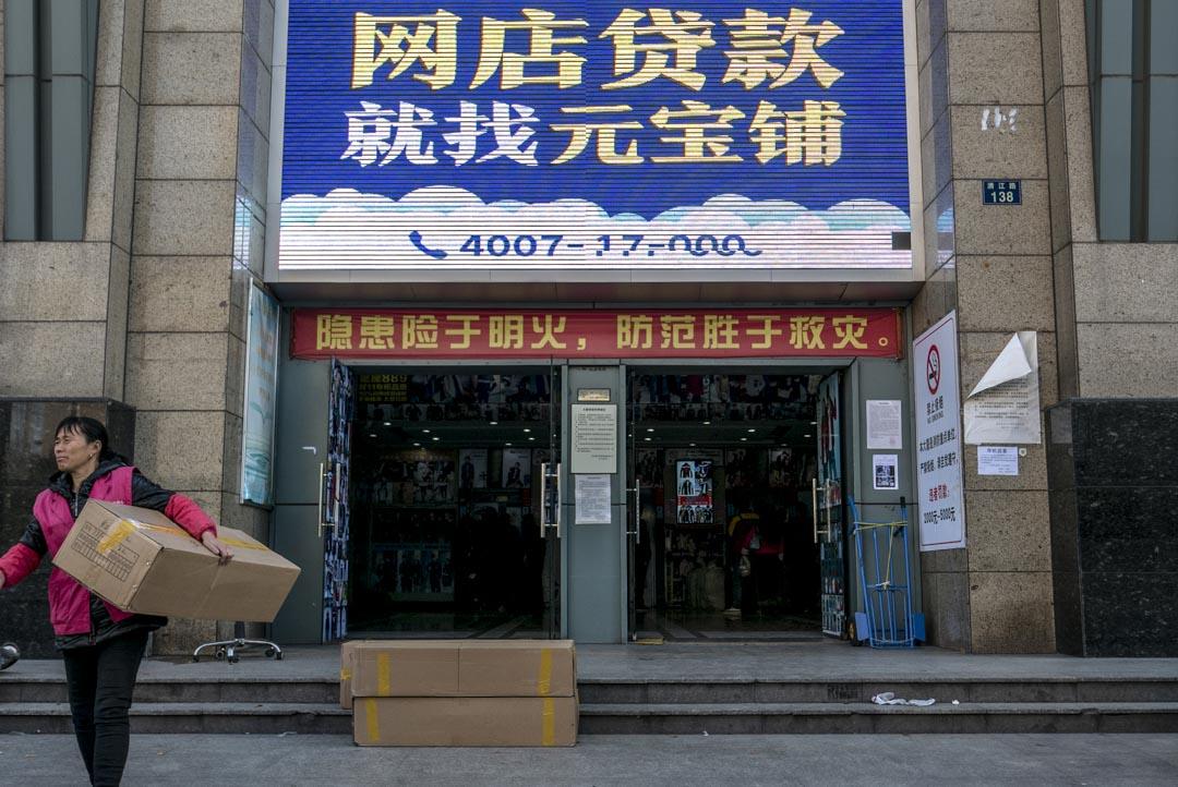 2015年11月27日﹐大樓門口貼著向淘寶店主借貸的大廣告,前有一名女士正運載著貨物 。