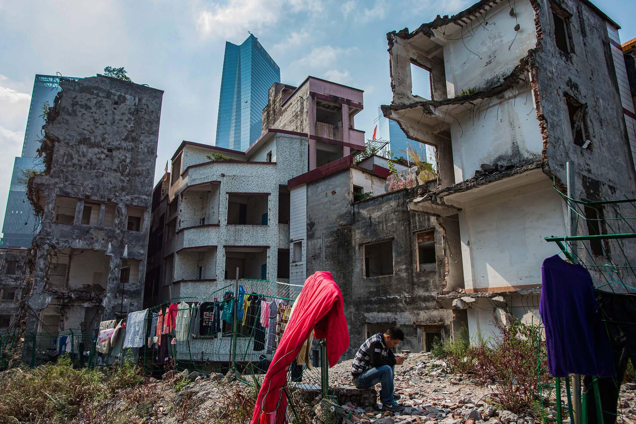 2016年3月3日廣州,一名男子坐在一個城中村内拆毀的住宅樓房旁。