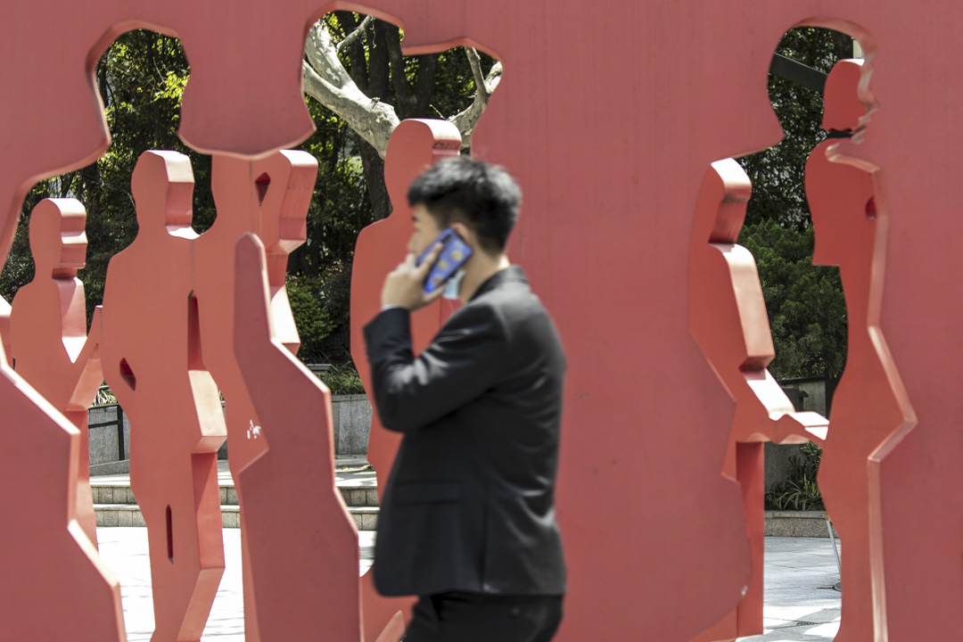 2021年4月10日,上海一名市民走過城中的一座雕像。
