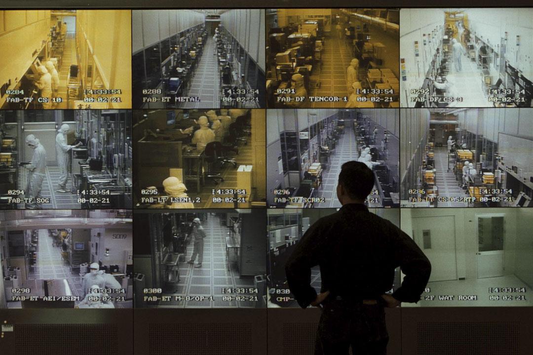 2000年5月1日,台灣新竹,聯電的參觀者在公司接待區的顯示器牆上觀察半導體製造。