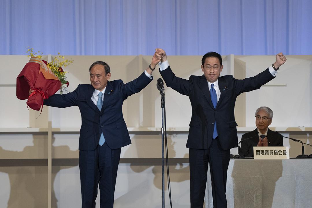 2021年9月29日,日本執政自民黨舉行黨總裁選舉。前外務大臣岸田文雄確認當選一刻,跟首相菅義偉攜手振臂慶祝。 攝:Carl Court / Getty Images