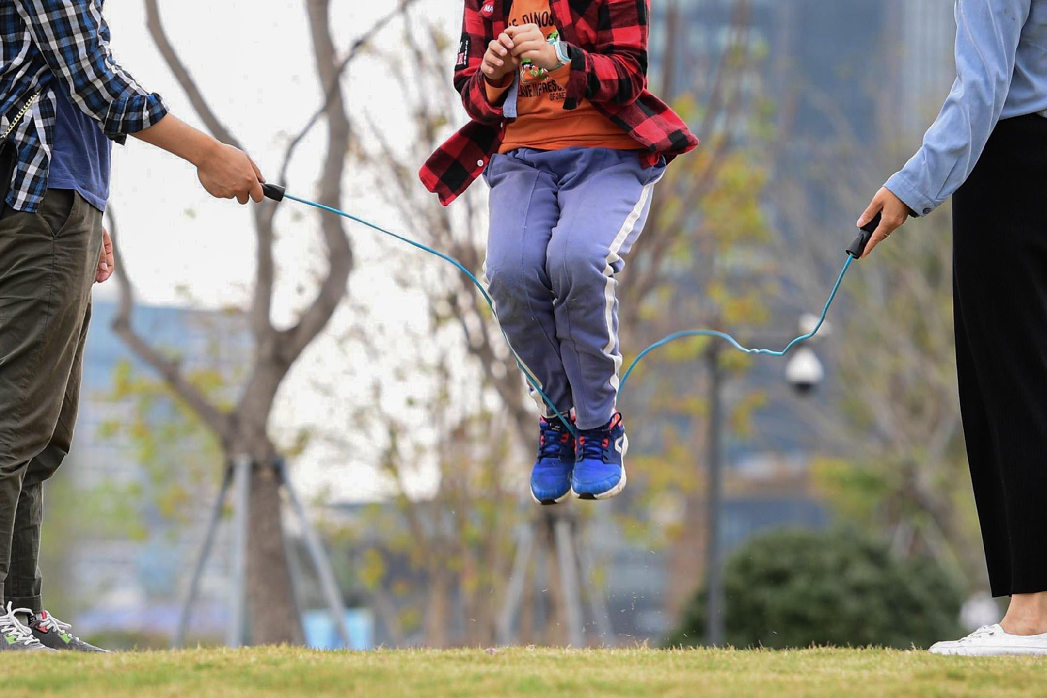 2020年3月8日中國深圳,一個戴著口罩的家庭在中國廣東省深圳市的公園跳繩。 攝:Chen Wen/China News Service via Getty Images