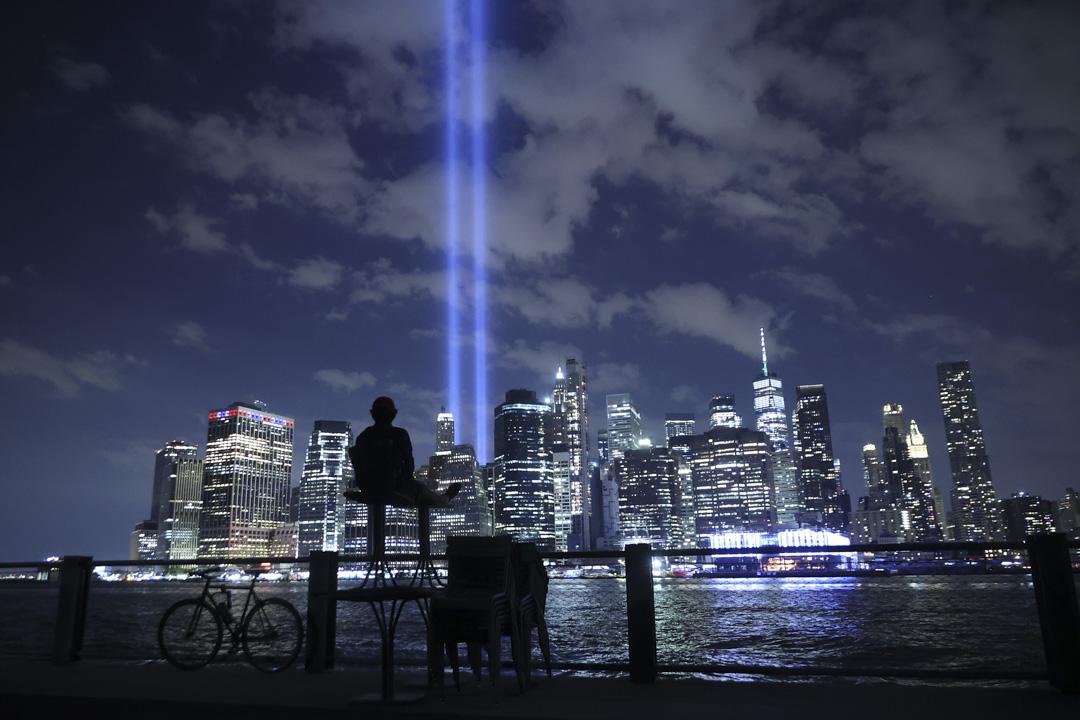 2021年9月7日,為紀念911 事件的受害者,光之致敬是一個紀念性公共藝術裝置,紐約一位市民觀看從曼哈頓下城射入天空的光。