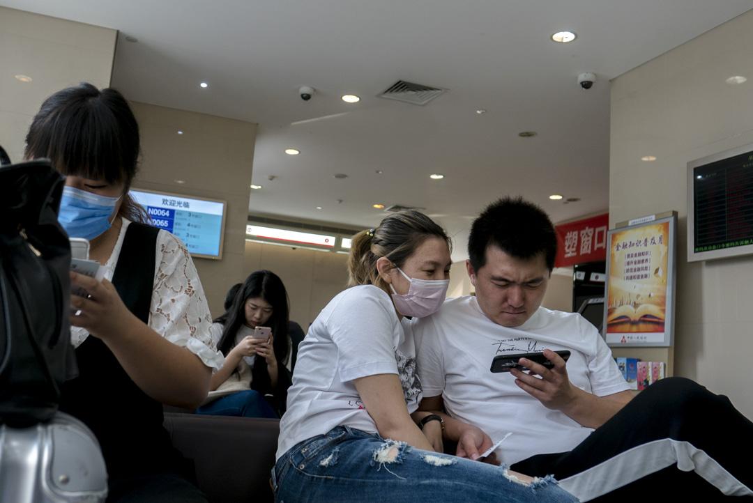 2017年9月23日﹐北京的年輕情侶在銀行等候時於手機上觀看視頻。