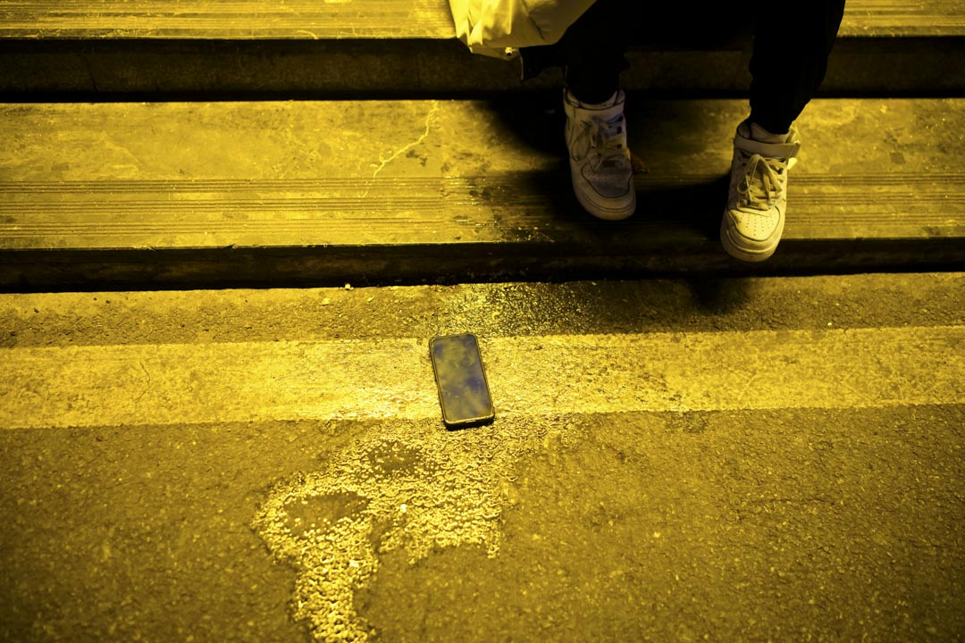 2020年12月12日中國湖北,一名男子的電話放在夜總會外的人行道上。 攝:Aly Song/Reuters/達志影像