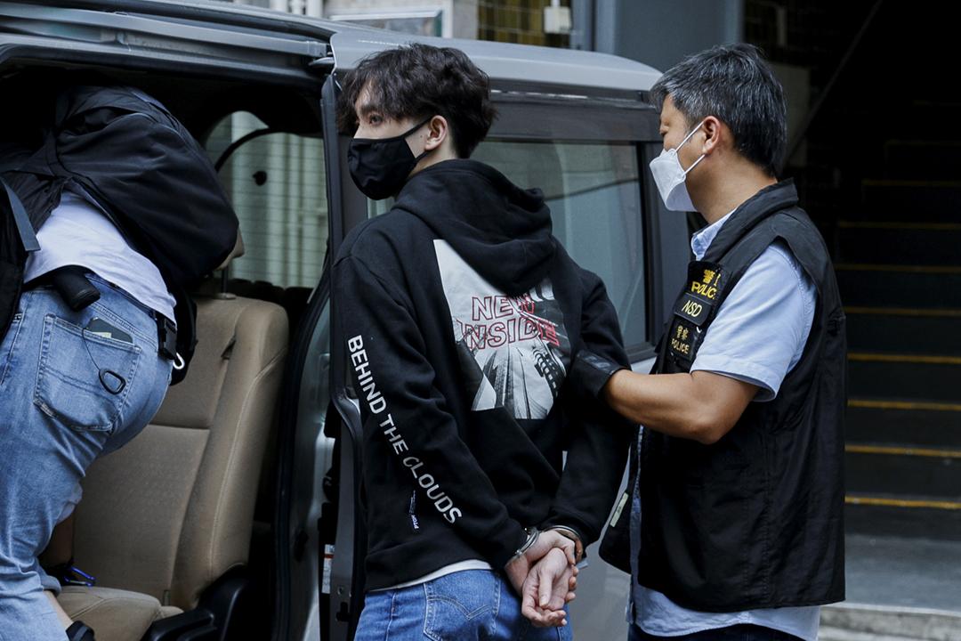2021年9月20日,香港警務處國家安全處警員將「賢學思政」召集人王逸戰押上一輛七人車。 攝:Tyrone Siu / Reuters