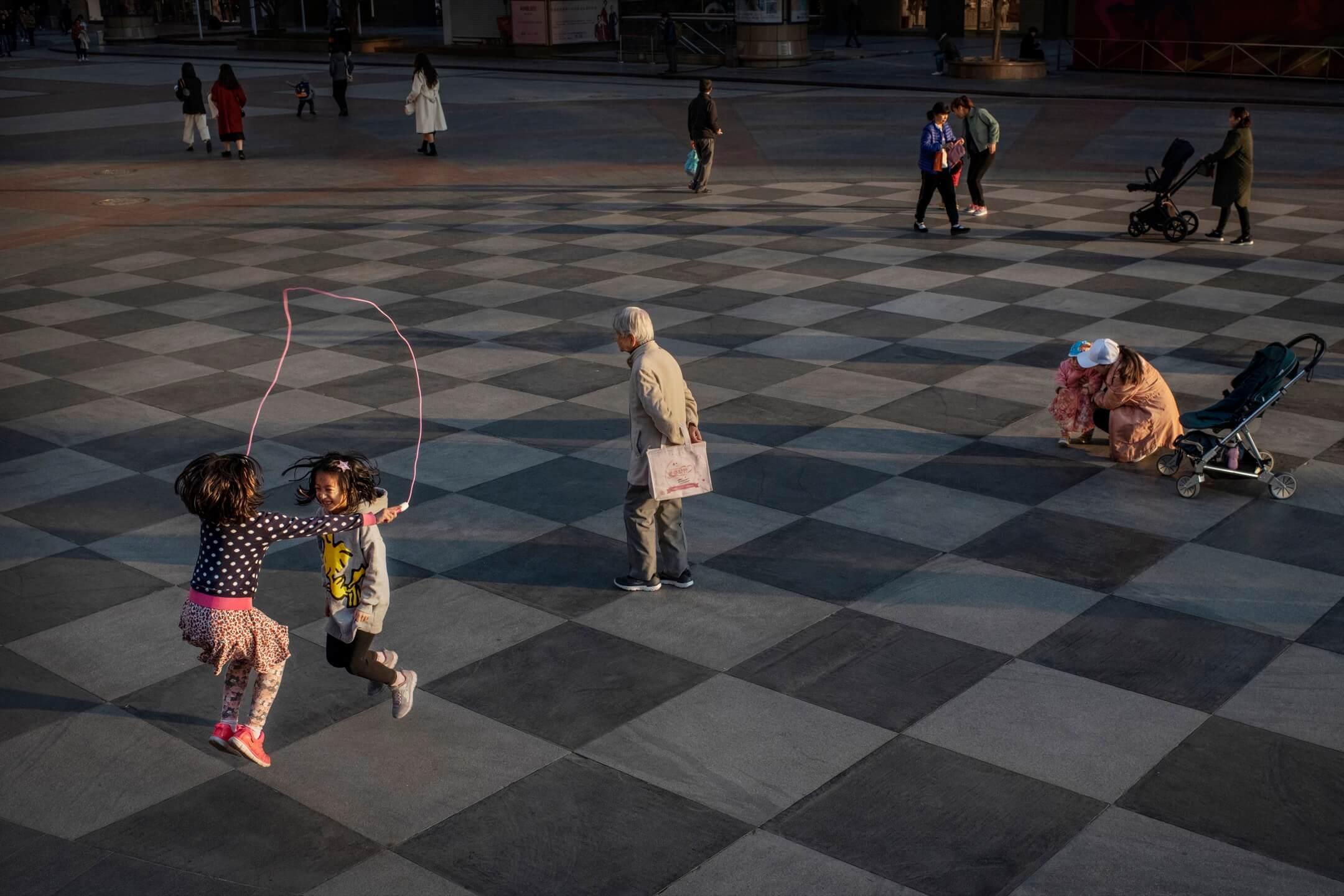2019年,中國首都北京,兩個女孩在廣場上跳繩。 攝:Kevin Frayer/Getty Images