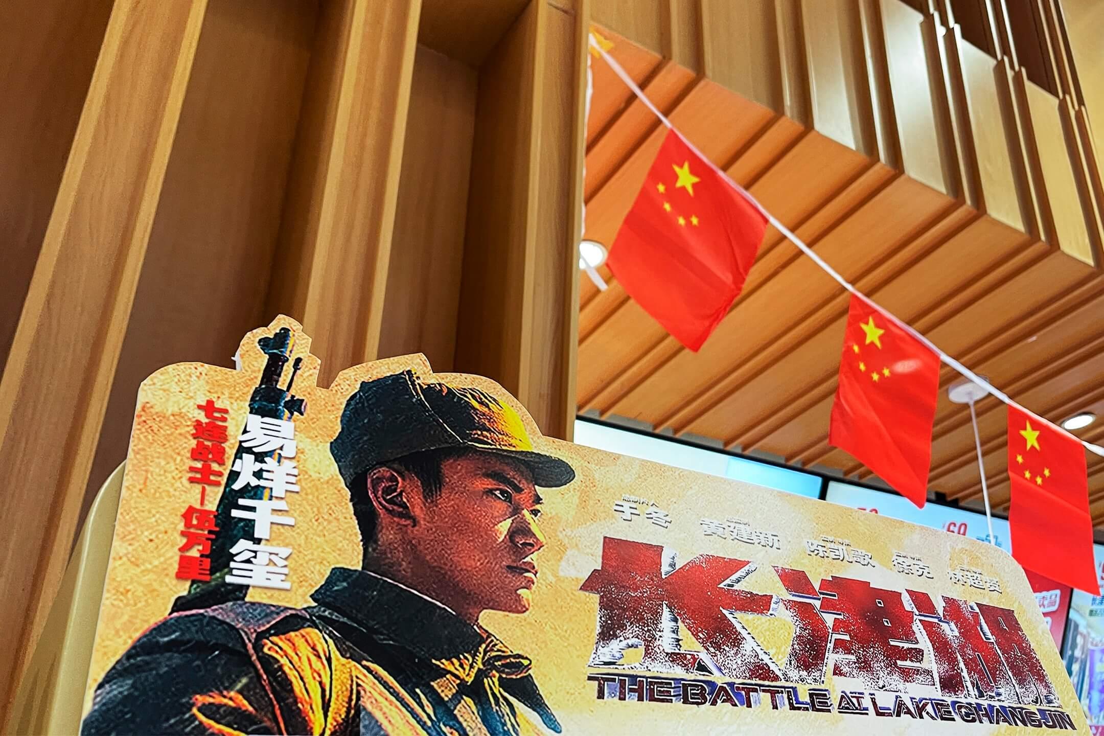 2021年9月30日,中國首都北京一家戲院門外,擺放著《長津湖》的電影海報,門口懸掛著國旗裝飾迎接國慶。 攝:VCG via Getty Images