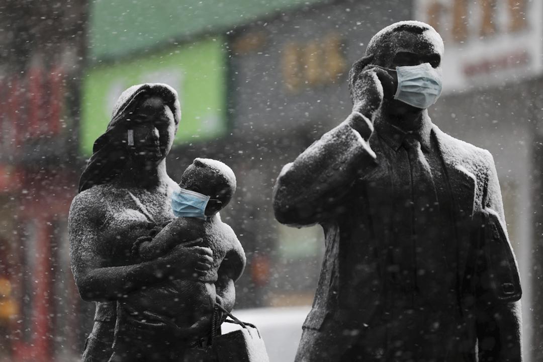 2020年2月15日在中國湖北省武漢市,有人為街頭上的一組雕塑戴上了防疫口罩。 圖片來源:China Daily via Reuters