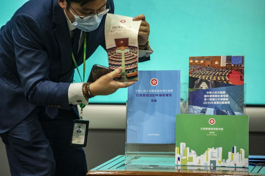 2021年10月6日,香港,特首林鄭月娥發表任內最後一份施政報告後,召開記者會回答記者提問。期間報告紙本從展示架翻倒,職員上前放回架上。