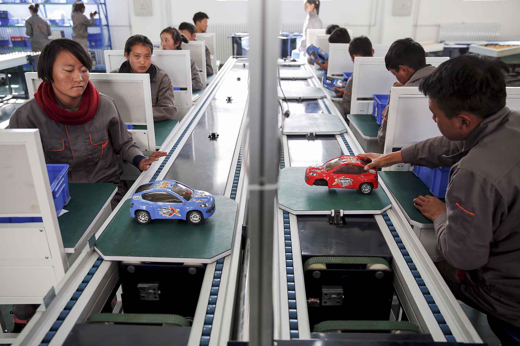 2015年11月19日西藏自治區拉薩市,一群外國記者參觀政府組織的一所職業學校,學生們在玩具汽車裝配線上工作。