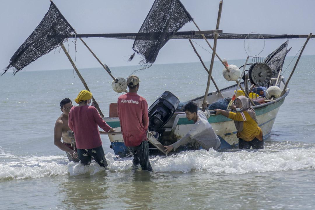 羅西拉瓦蒂與一眾漁民把漁船拉到岸邊。