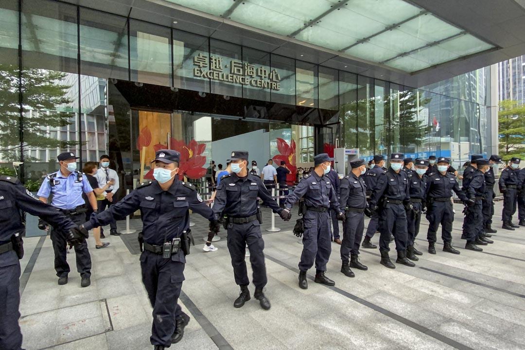 2021年9月13日,深圳恆大總部外的保安在大廈外築起人鏈,抵擋那些要求償還貸款和金融產品的市民。