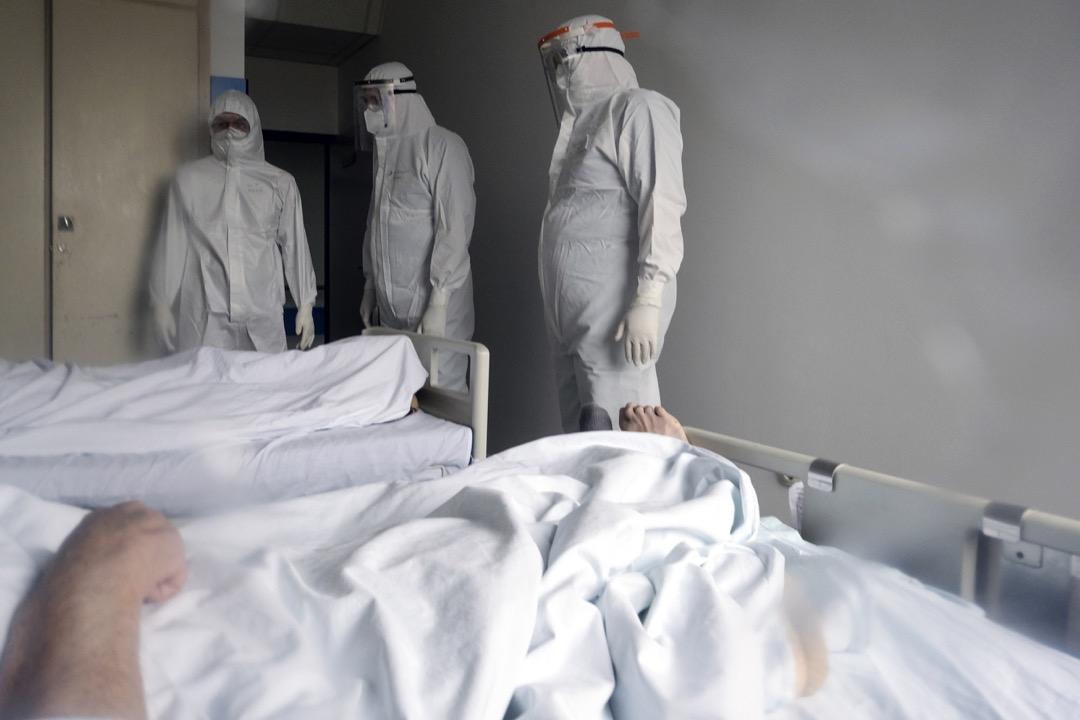 2020年11月19日,波黑首都薩拉熱窩,穿上保護衣的醫生和護士觀察病房內的2019冠狀病毒患者的情況。