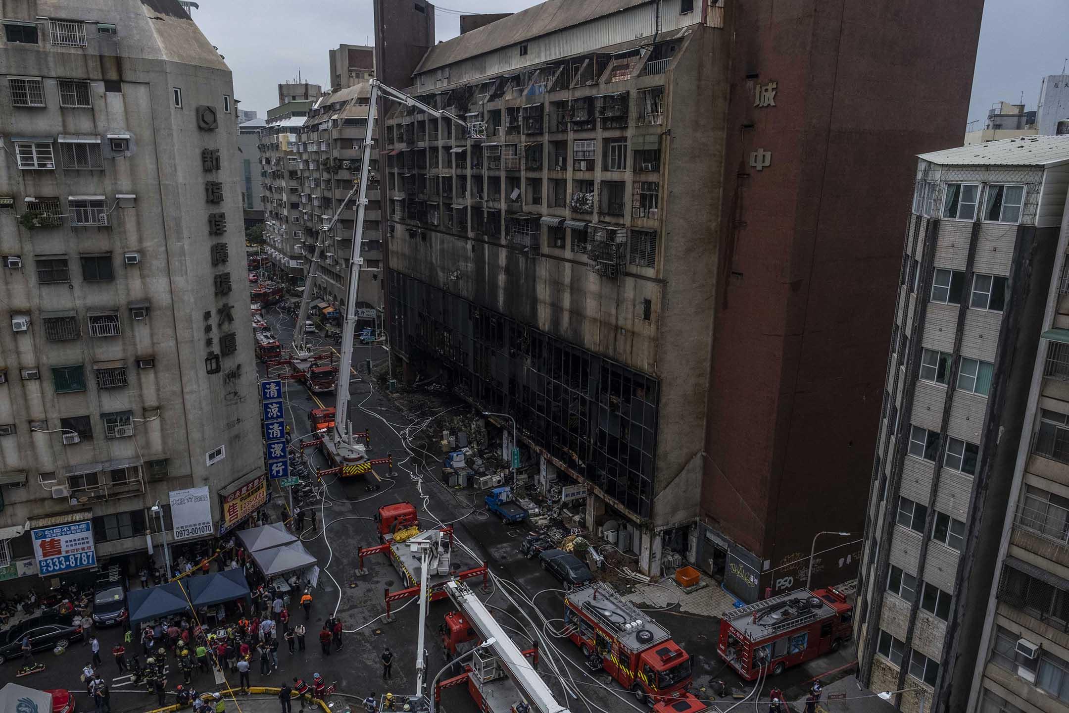 2021年10月14日台灣高雄,消防隊員在火災後救援。 攝:Lam Yik Fei/Getty Images