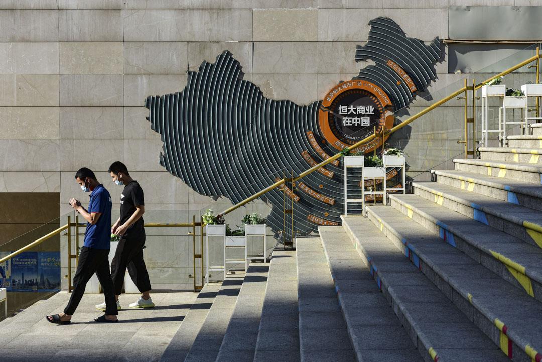 2021年9月22日﹐北京兩名男子在朝陽區恆大的中國發展藍圖前路過。  攝:Sheldon Cooper/SOPA Images/LightRocket via Getty Images